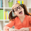 Little girl stops homework reading to stick her tongue out — Stock Photo #40398335