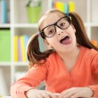 Stock Photo: Little girl stops homework reading to stick her tongue out