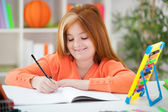 Cute little red-haired girl doing her homework at home — Stock Photo