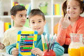 Young brothers and sisters together learn math on abacus — Stock Photo