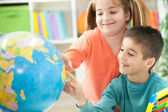 Young brother sister shows place on the globe — Stock Photo