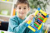 Young boy at home working on the abacus — Stock Photo