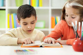 Young brother and sister learn how to read at home — Stock Photo