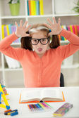 Little girl stops homework reading to stick her tongue out — Stock Photo