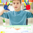 Boy with hands painted in colorful paints ready for hand prints — Stock Photo