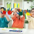Three happy little kids with painted hands — Stock Photo