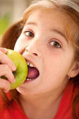 Cute little girl eating an apple — Stock Photo