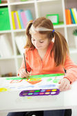 Red-haired girl with pigtails drawing with watercolors on the pa — Stock Photo