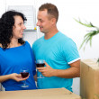Happy couple celebrating moving to new house with red wine — Stock Photo #41750811