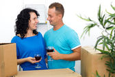 Happy couple celebrating moving to new house with red wine — Photo