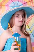 Little girl in blue summer hat drinking juice — Stock Photo