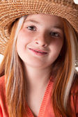 Portrait of little red-haired girl with freckles and a straw hat — Stock Photo