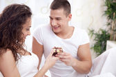 a smiling young man gives a girl a gift  — Stock Photo