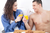 Beautiful young couple having breakfast in bed together — Stock Photo