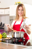 Beautiful housewife cooking and testing the food in  kitchen — Stok fotoğraf