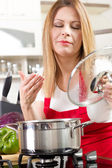 Beautiful housewife cooking and testing the food in  kitchen — Stock Photo