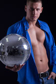 Young sexy man holding a disco ball — Stockfoto