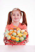 Young smiling freckles girl holding a basket of Easter eggs — Stock fotografie