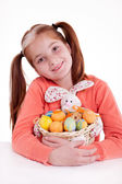 Young smiling freckles girl holding a basket of Easter eggs — Stok fotoğraf
