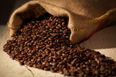 Coffee beans in burlap sack against dark wood — Stock Photo