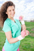 Happy Young Woman Practicing with dumbbell in park — Stock Photo