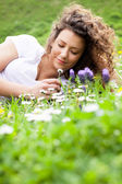 Young beautiful girl laying on the flowers field, summer concept — Stock Photo