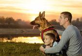 Vader en zoon en duitse herder in de natuur kijken naar de zonsondergang — Stockfoto