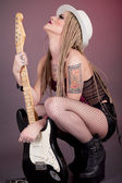 Beautiful woman punk rocker with electric guitar — Stock Photo