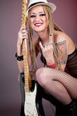 Beautiful punk girl with lots of tattoos posing with guitar — Stock Photo