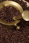 Coffee beans and old brass cup — Stock Photo