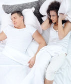 Snoring man and young woman. Couple sleeping in bed.  — Stock Photo