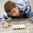 Little boy drawing with chalk outdoors — Stock Photo