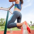 Sport woman doing pull ups outdoors — Stock Photo #48196945