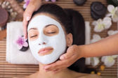 Spa therapie voor jonge vrouw gezichtsmasker gelet op de salon van de schoonheid — Stockfoto