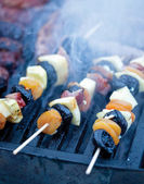 Meat and vegetable skewer on barbecue grill with fire  — Stock Photo