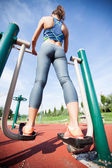 Woman exercising with  elliptic bike in public park on sunny day — Stock Photo