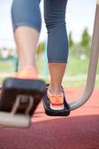 Woman legs on elliptic bike in public park — Stock Photo
