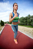 Running woman. Female runner in front of blue sky, low angle — Foto Stock