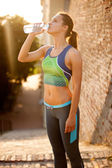 Sporty woman drinking water outdoor on sunny day  — Stockfoto
