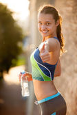 Relaxing after jog. Beautiful young woman holding bottle with wa — Stock Photo