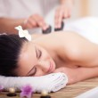 Beautiful woman having a wellness back massage with hot stones — Stock Photo #49012873