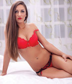 Photo of female model lying in red lingerie on bed — Stock Photo