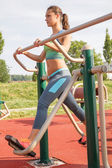 woman exercising with  elliptic bike in public park on sunny da — Stock Photo