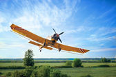 Low Flying Crop Duster against a blue sky — Stock Photo