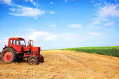 Old red tractor during wheat harvest on cloudy summer day — Foto Stock