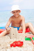 Little boy at tropical beach making sand castle  — Stock Photo