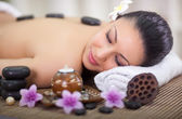 Beautiful woman in spa salon with hot stones in back — Stock Photo