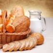 Bread products in basket and jug of milk — Stock Photo