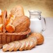 Bread products in basket and jug of milk — Stock Photo #12182739