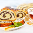 Macro of poppy seed roll slices and tea — Stock Photo